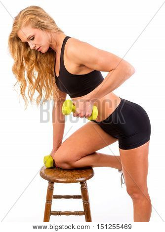 Fitness model posing in workout outfit using stool
