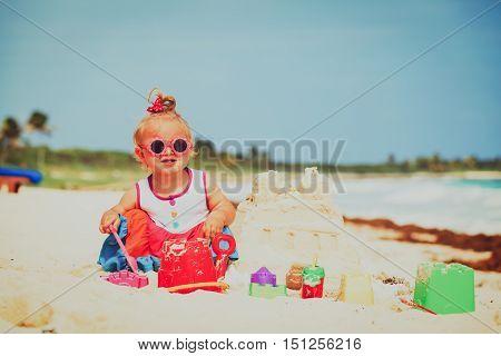 cute little girl building sandcastle on tropical beach