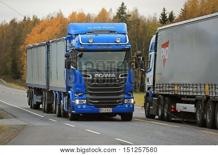 KAARINA FINLAND - OCTOBER 9 2016: Blue Scania R580 combination vehicle of Kosti Saukko Oy meets another Scania truck on the road on a cloudy day in autumn.