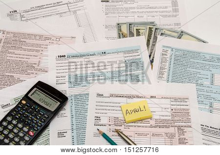 Federal Tax forms 1040 with pen calculator and dollar