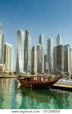 DUBAI, UAE - OCTOBER 09, 2016.  A traditional Arabic wooden dhow in Dubai Marina with modern skyscrapers in the background including Infinity Tower