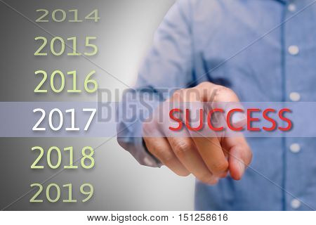 bussinessman hand pointing success text for 2017. targets concept