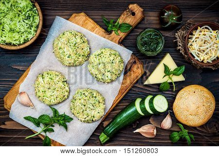 Raw ingredients for vegetarian dinner recipe. Preparing veggies cutlets or patties for burgers. Zucchini quinoa veggie burger with pesto sauce and sprouts. Top view overhead flat lay