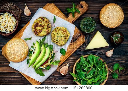 Zucchini quinoa veggie burger with pesto sauce and sprouts. Vegetarian burger on a cooking sheet ready to prepare hamburger. Top view overhead flat lay