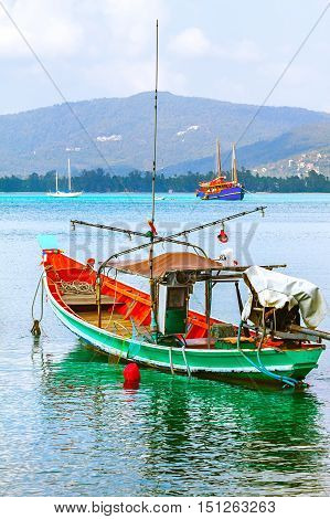 Wooden fishing boat green. The sea is turquoise and the island.