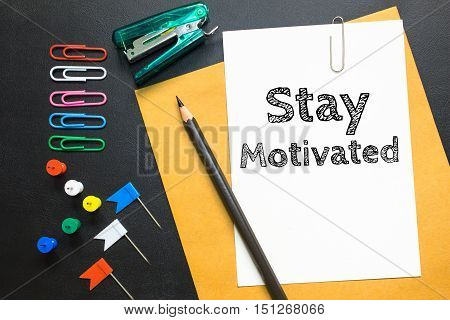Text Stay motivated on white paper / business concept