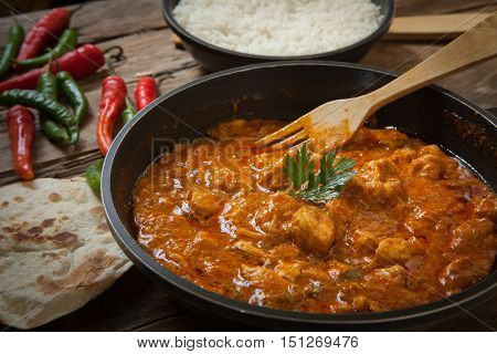 butter chicken curry on pot with green and red chili pepper