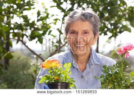 Senior Woman Outside in the garden getting ready to plant flowers with a big smile.