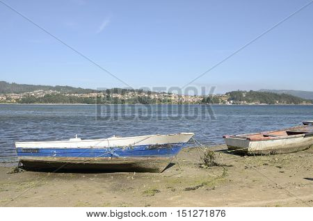 Rustic fishing boats at the shore of the ria in Combarro a village of the province of Pontevedra in the Galicia region of Spain.