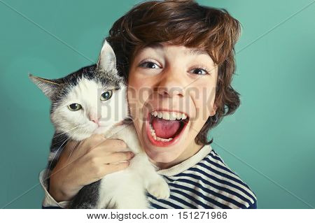 preteen handsome boy with tom cat close up cuddle photo on blue wall background