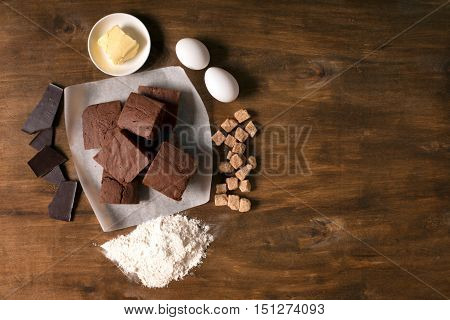 Chocolate brownie cake and ingredients. Top view wooden background