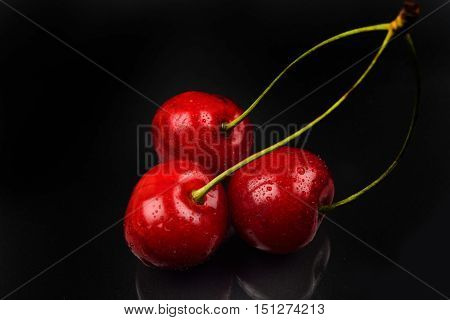 Two Red Cherries And One Broken Against Reflective Black Background. Selective Focus. Lights And Sha