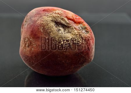 Spoiled And Moldy Peach On Old Dark Reflective Table, Unhealthy Eating