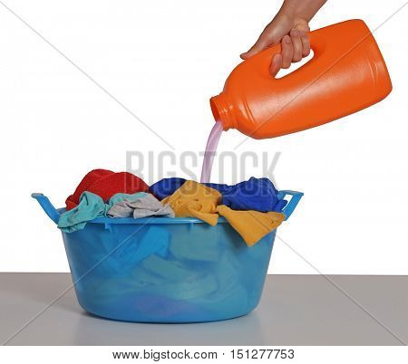 Housewife pouring detergent soap on laundry basket.