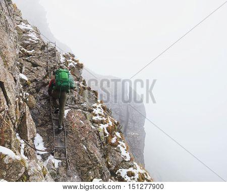 tourist ascending the peak with ladder in foggymountain. High Tatras, Zakopane, Poland