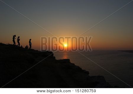 Silhouettes of five people on mountainside on a background of sunset and sea