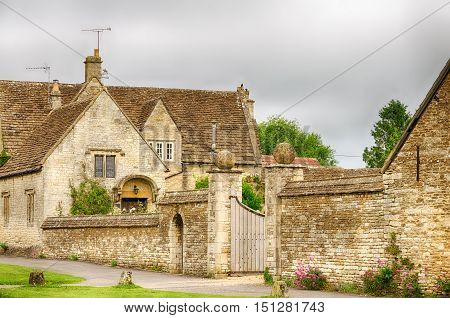 Stone wall around home garden in Castle Combe Village in Wiltshire, England on overcast day.