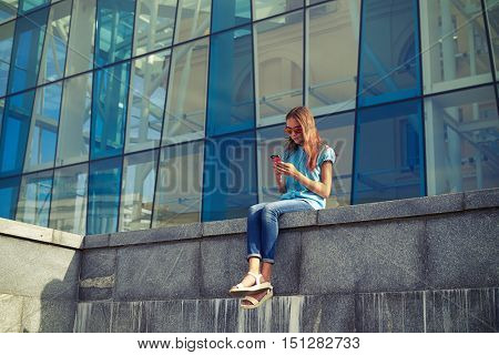 Trendy stylish girl  sitting alone and using mobile phone in the downtown