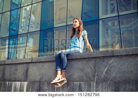 Young casual girl looking far away while sitting against a business center