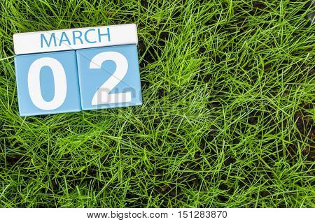 March 2nd. Day 2 of month, calendar on football green grass background. Spring time, empty space for text.
