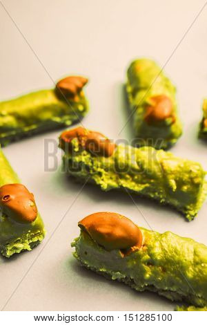 Cake pieces resembling spooky monster witches fingers toppled with pistachio and chocolate icing halloween treats