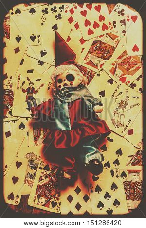 Spooky evil clown toy doll on scattered casino playing cards background black magic and fortune telling