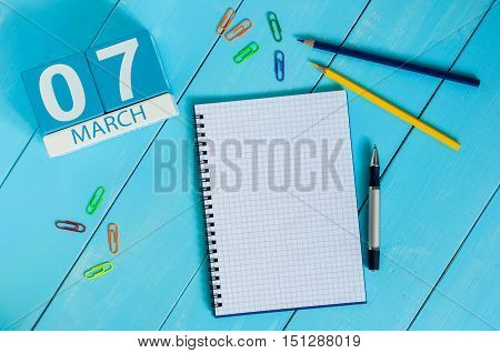 March 7th. Day 7 of month, calendar on blue wooden table background. Spring time, empty space for text.