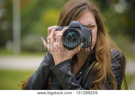 Young woman holding a professional DSLR camera, taking a picture