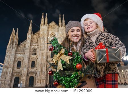 Mother And Child Showing Christmas Tree And Gift In Milan, Italy