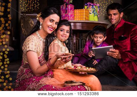 Indian family in traditional wear lighting oil lamp and celebrating Diwali or deepavali, fesitval of lights at home. Husband holding a plate full of oil lamp indoors.