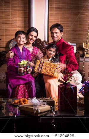 Indian family celebrating diwali festival or birthday by exchanging or showing gifts, two generations of indian family and gifts and sweets, diwali or festival or happiness concept