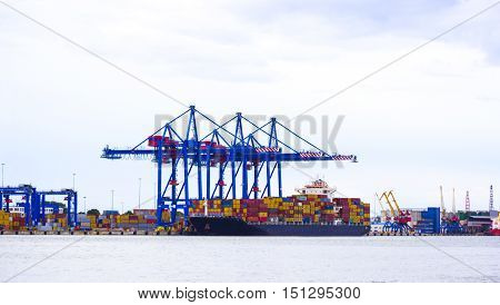 Tilt-shift panoramic view of sea port with ship cargo containers and lorry. Miniature tilt shift lens effect.
