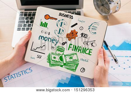 Close up of male hands holding notepad with creative finance sketch above workplace with laptop business report and other items. Financial growth concept