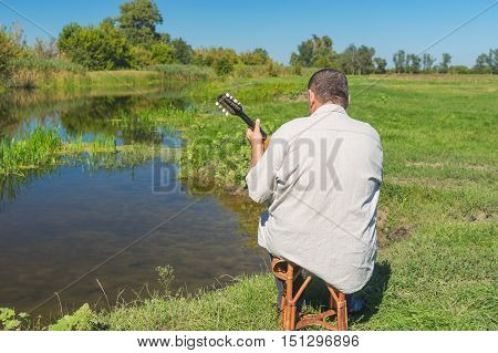 Ukrainian senior man having rest on a riverside sitting on a wicker stool and playing with mandolin