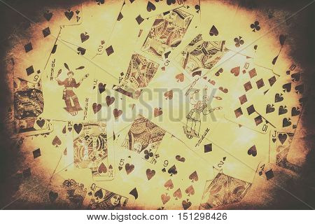 Vintage card games and poker background on a scattered playing deck of casino cards with texture and vignette