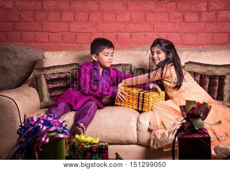 Portrait of indian children with diwali gifts, people and diwali celebration, indian kids sitting with gifts on sofa or couch and celebrating diwali festival
