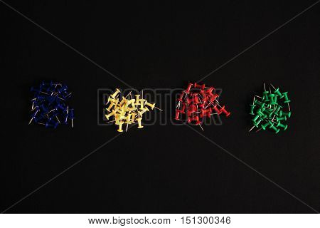 Drawing pins of different colors on a black table top view