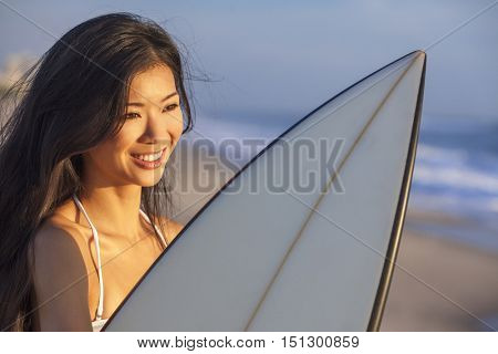 Beautiful sexy young woman surfer girl in bikini with white surfboard on a beach at sunset or sunrise