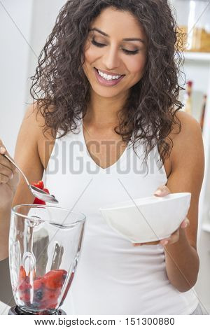 A beautiful happy young woman or girl with perfect teeth preparing fresh fruit smoothie in her kitchen blender at home