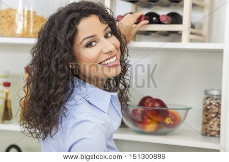 Happy smiling young woman reaching for and choosing bottle of red wine from rack at home