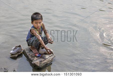 Chittagong Bangladesh February 25th 2016: young bangladeshi boy washing his shoes in a river