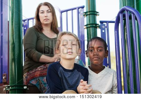 Two Boys Sitting With Mother At Playground