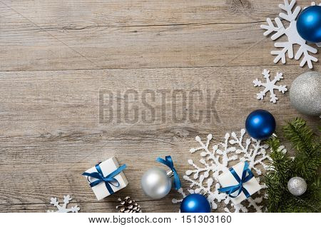 Christmas background with decorations and white gift boxes with blue ribbon on wooden table with copyspace. Top view of xmas decorations with fir branches, snowflakes and silver balls and presents.
