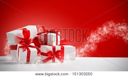 Group of small gifts wrapped with red ribbon on white table with copy space. Five little presents for christmas or birthday party. Set of gift boxes over a red shiny background.