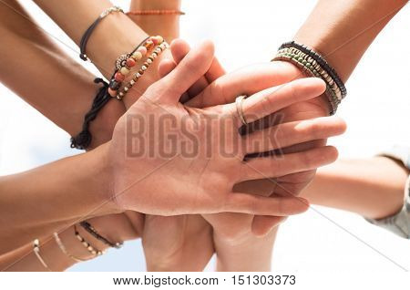 Closeup hands of a group of people. Low angle view of multiethnic friends stacking hands over each other. Unity and solidarity cocept.