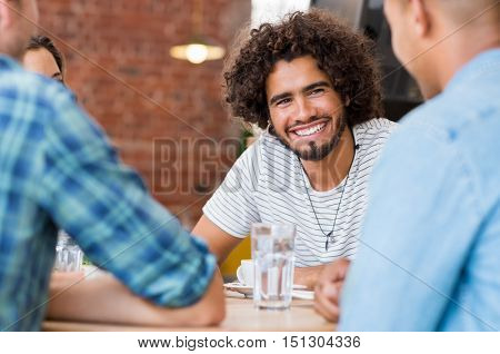 Cheerful young man sitting with friends at cafe. Portrait of multiethnic guy talking with his friends at coffee shop. Close up face of a young man with beard and curly hair listening his friends.