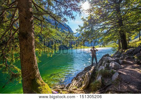 Young man photographing Seealpsee with the Swiss Alps (mountain Santis) Appenzeller Land Switzerland