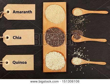Quinoa, chia and amaranth seeds in wooden spoons on a black stone background with lables. Super foods concept. Gluten free grains. Place for text. Lovely light gradient. Top view.