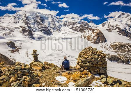 Young man enjoying the stunning view of Bernina massive and Morteratsch glacier from Diavolezza mountain canton Graubunden. Diavolezza is one of the ski areas of the Upper Engadin near Sankt Moritz Switzerland.