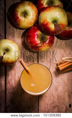 High Angle Still Life of Glass of Fresh Pressed Apple Juice or Cider with Sticks of Cinnamon and Ripe Apples on Rustic Wooden Table